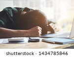 Small photo of Burnout Syndrome, Man sleeping at his desk working over a laptop,Tried overworked, Freelance man working overload, Young business owner at home office,man feel tried and nap on desk.