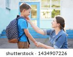 Small photo of mother accompanies the child to school. mom encourages the student to accompany him to school. A caring mother looks tenderly at her son going to school.positive boy having fun going to primary school