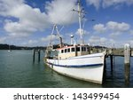 Small photo of An old fishing boat in Totara North pier at Whangaroa harbor in Northland, New Zealand.