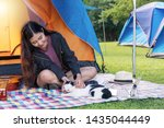 Stock photo cheerful young woman sitting in front tent with hat and guitar while enjoy playing white back cat 1435044449