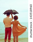 Summer vacation concept. Couple standing on beach near water and holding black umbrella. Hipster style. Copy-space. Outdoor shot - stock photo