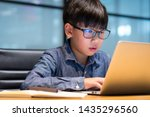 Smart asian preteen boy wearing blue light blocking glasses using his laptop to study lesson through online learning from home during Covid-19 pandemic, city lockdown and social distancing. - stock photo