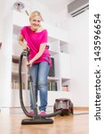 Young woman cleaning and mopping floor at home. - stock photo