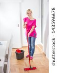 Beauty woman cleaning and mopping floor at home. - stock photo