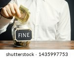 Small photo of A man puts dollars in a glass jar with the word Fine. Saving money and paying a fine. Punishment for a crime and offense. Financial punishment. Violations of traffic laws. Fraud. Monetary penalty.