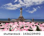 Buddhist culture statue of the goddess guanyin Nanshan on Hainan Island in China near the ocean with lotus flowers