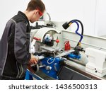 Worker handles metal at lathe - stock photo