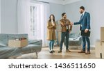 Small photo of Professional Real Estate Agent Shows Bright New Apartment to Young Couple. Successful Young Couple Becoming Homeowners, Seal the Deal with Real Estate Broker by Handshake. Bright Home with Big Windows