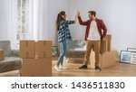 Small photo of Happy Young Couple Moving in Into New Apartment, Carrying Cardboard Boxes with Stuff, Having Fun, Give High Five. Young Boyfriend and Girlfriend Start Living Together, Unpacking Stuff.