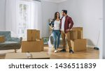 Small photo of Happy Young Couple Moving Into New Apartment, Carrying Cardboard Boxes with Stuff and Poses on Camera. Young Boyfriend and Girlfriend Start Living Together, Unpacking Stuff.