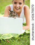 Stock photo beautiful girl with her kitty and laptop outdoors 143670070