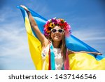 Happy Ukrainian girl carries fluttering blue and yellow flag of Ukraine against blue sky and sea background. Ukrainian flag is a symbol of independence. Celebrate Constitution day, Kyiv day, Kiev day