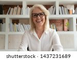 Small photo of Happy old online teacher tutor look at camera give educational training class lecture teach by webcam, smiling mature business woman talk to webcam make video conference call sit at table in library