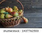 Small photo of Green pears with red sidewise lie in the wicker basket and a wooden table.