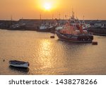 RNLI lifeboat and other boat moored and anchored in a harbour at sunset in Portrush, Co Antrim, Northern Ireland