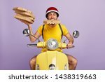 Small photo of Funny deliveryman overload with pizza boxes, keeps one package in mouth, rides fast moped, dressed in special uniform, isolated on purple background. Food courier busy working, serves customers