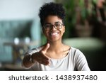Small photo of Happy african American young woman in glasses stretch hand for handshake greeting introducing to someone, smiling black biracial millennial female hr agent in spectacles get acquainted at meeting