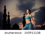 Arabian nights. Beautiful girl in belly dance costume with a silhouette of eastern palace in the starry sky - stock photo