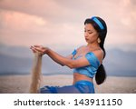 Beautiful brunette girl in belly dance costume looking at the sand running through her hands at sunset - stock photo