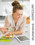 happy young housewife eating... | Shutterstock . vector #143922190