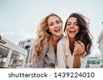Small photo of Appealing long-haired girls posing on sky background. Laughing ladies enjoying weekend together.