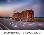 Small photo of A loaded timber truck transports timber logs with an overload on the highway, black smoke. The concept of transportation of timber and wood, copy space, business