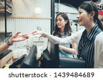 Small photo of small business payment people and service concept. happy woman paying money cash to seller at cafe drink beverage vendor. two asian girls purchase local specialty meal in outdoor market street.