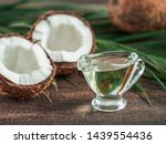 Small photo of Liquid coconut MCT oil and halved coco-nut on wooden table. Health Benefits of MCT Oil. MCT or medium-chain triglycerides, form of saturated fatty acid.
