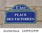 Victories square. White and blue street name sign on a stone facade. Paris, France. French text: Place des Victoires