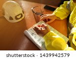 Small photo of Safe work practice top view of young trained administrator writing job hazards analysis working at height risk assessment safety control permit prior to start morning shift during shut down