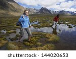 Two Hikers Wading Through Pond...