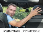 Small photo of mature professional man driving a car in reverse