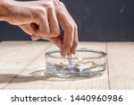 Small photo of Hand stubbed out cigarette in a transparent ashtray on wooden table
