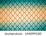 Close up of metal twist fence with orange light background - stock photo