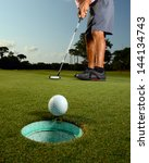 Golfer Putting Ball In Hole On...