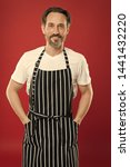 Small photo of Skilled and confident. Senior cook wearing bib apron. Bearded mature man in striped apron. Mature person in cooking apron. Aged master of the household. Doing household. Home cooking.