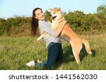 Stock photo young woman with adorable akita inu dog in park 1441562030