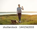 Stock photo young woman walking her adorable brussels griffon dogs near river 1441562033