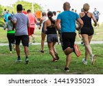Small photo of Runners running on grass away from the camera during a 10K summer series race at Sunken Meadow State Park.