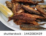Small photo of Fried vendace fishes and slice of lemon on white plate. Also known as European cisco, Muikku in Finnish is traditional Finnish delicacy and the Finns enjoy eating this.