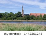 View of the tower of the baroque style church of our Savior (Vor Frelsers Kirke) from the lake near Christiania area, Copenaghen, Denmark