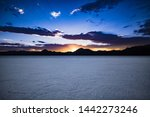 View across the Bonneville Salt Flats in Utah, with the sunset glowing behind the distant, silhouetted mountains.