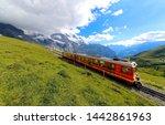 Small photo of A cog wheel train travels on famous Jungfrau Railway from Kleine Scheidegg to Jungfraujoch station ( top of Europe ) on the green grassy hillside, in Berner Oberland ( Bernese Highlands ), Switzerland
