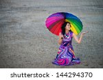 Smiling woman with colorful umbrella sitting on the ground under the rain - stock photo