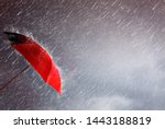 Small photo of Red umbrella against the storm,sky background and black cloud group and rain, preventing rain and wind hazards,saving planning, and health care,thunderstorm with insurance concept, accident protection