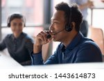 Small photo of Smiling young african businessman call center agent wear wireless headset laugh at workplace, cheerful happy black male telemarketer operator have fun at work break in customer service support office
