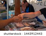 Stock photo man at dutch markets in the netherlands paying a lady for the fish called herring to eat 1443912443