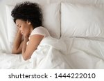 Small photo of Serene calm african american woman sleeping in comfortable bed lying on soft pillow orthopedic mattress, peaceful young black lady resting covered with blanket on white sheets in bedroom, top view