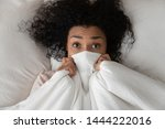 Stock photo surprised scared funny african girl lying in bed covering face with blanket young black woman 1444222016