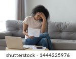 Small photo of Stressed african woman holding papers calculate domestic bills at home worried about bankruptcy financial problem bank debt, depressed sad black lady frustrated about lack of finances sit on sofa